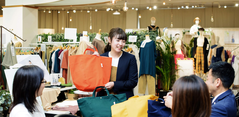 バッグを手にプレゼンする女性社員の写真